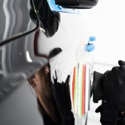Buffing and polishing car. Car detailing. Man holds apolisher in the hand and polishes the car